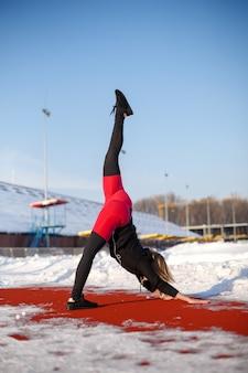 雪に覆われたスタジアム、フィット感、スポーツライフスタイルの赤いランニングトラックで運動をストレッチバイオレットレギンスの若い白人女性金髪