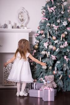 Маленькая девочка увидела гору подарков, на которой сидит плюшевый мишка