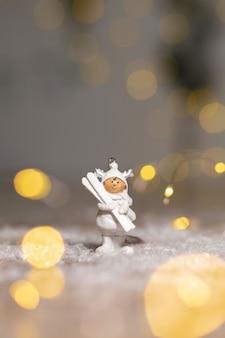 白いスキーと白いスーツの小さな男の像