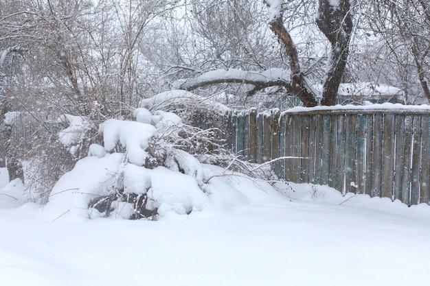 木の板の冬の古い老朽化したガタガタしたフェンス。吹雪