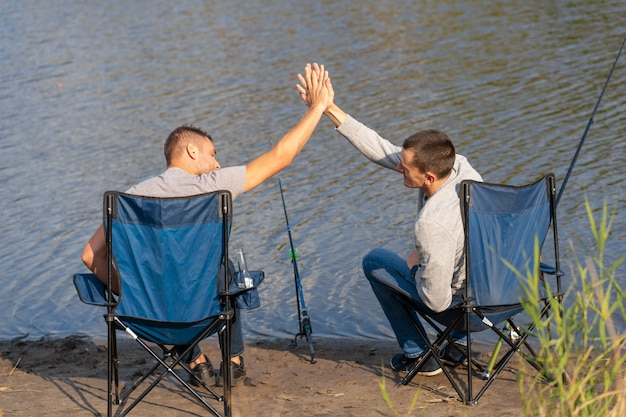 Концепция отдыха и людей, счастливые друзья с рыболовными удочками на пристани берегом озера.