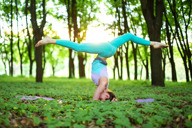 若いスポーツ少女は、やめられた緑の夏の森、ヨガのアサンの姿勢でヨガを練習しています。瞑想と自然との一体感