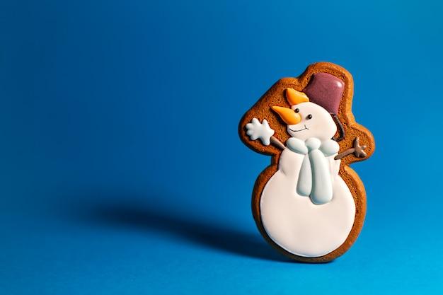 Пряники печенье милый снеговик на синем. традиционная рождественская еда. рождество и новогодний праздник.