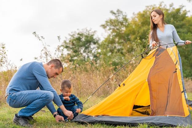 幼い息子と幸せな家族は、キャンプテントを設定します。幸せな子供時代、両親とのキャンプ旅行。子供がテントの設置を手伝います