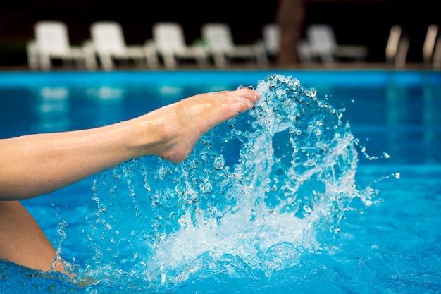 Сексуальная женская нога. девушка сидит на краю бассейна брызг воды ногами.
