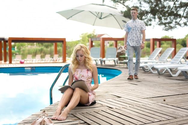 Молодая сексуальная девушка читает меню ресторана, сидя на краю бассейна в роскошном отеле. парень подходит к ней сзади