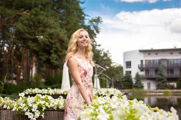 若い魅力的なブロンドの女の子は、公園の自然の美しさを楽しんでいます