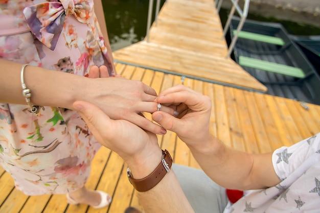 若いかわいい男は、木製の桟橋で彼の膝の上に立って、彼の最愛の女の子に結婚提案をします。木製の桟橋でのロマンスと愛。