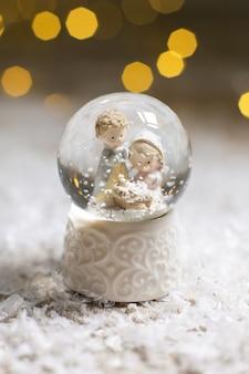 Декоративные статуэтки на рождественские темы. стеклянный шар со снежинками, в котором двое мужчин смотрят на колыбель, символ рождества христова