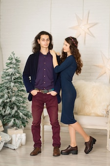 Молодая пара позирует в рождественские украшения в стиле ретро