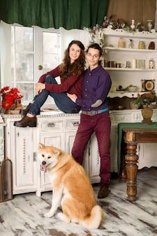 秋田犬の品種の犬とドレッサーの上に座ってポーズ陽気な若いカップル。レトロなスタイルのクリスマスの装飾で