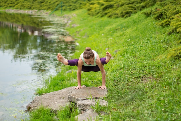Стройная молодая брюнетка-йога выполняет сложные упражнения йоги на зеленой траве летом на фоне природы
