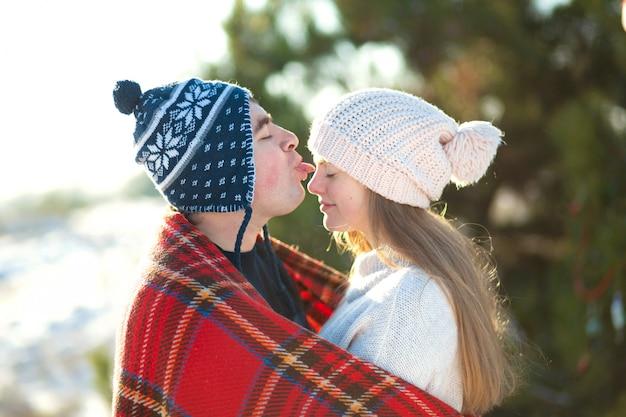 Зимняя прогулка по лесу. парень с девушкой поцеловал завернутый в красный клетчатый плед