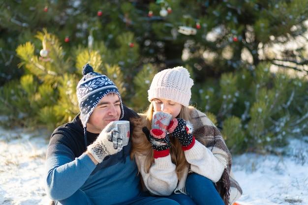 愛の若いカップルは、マシュマロと一緒に温かい飲み物を飲み、冬の森の中に座って、暖かく快適なラグに隠れて、自然を楽しみます。彼らは森で熱い飲み物を飲みながら話し、笑います