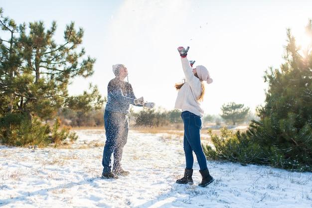 Влюбленные играют в снежки зимой в лесу. кидай друг другу снег. смеяться и хорошо провести время