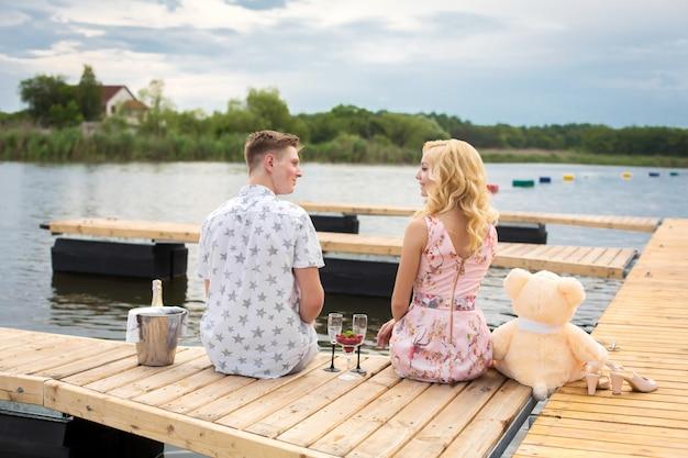 ロマンチックなデートのサプライズ。若い男と木製の桟橋の女の子。