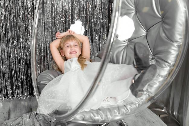 少女は椅子で銀のボールとガラスのボウルを果たしています。雪の女王カバー。