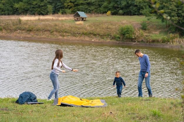 幼い息子と幸せな家族は、キャンプテントを設定します。