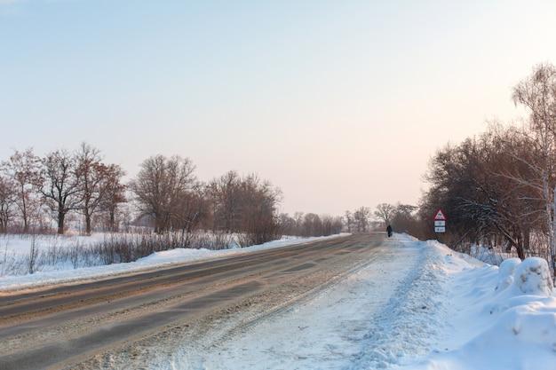 冬の道路はよく整備されていません。雪が散らばって田舎の道。吹きだまりのある冬景色