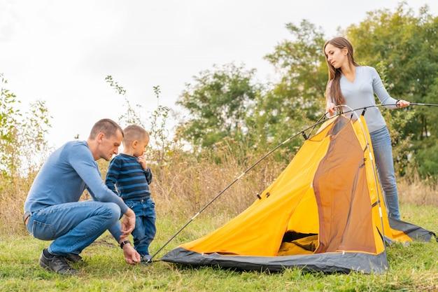 幼い息子と幸せな家族は、キャンプテントを設定します。幸せな子供時代、両親とのキャンプ旅行。