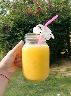 プルメリアの花とガラスのカップで新鮮なマンゴージュース