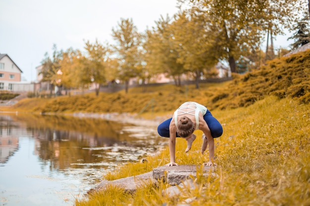 若いスポーツ女性が川沿いの黄色い芝生でヨガを練習し、ヨガのアサンの姿勢を使用します。瞑想と自然との一体感