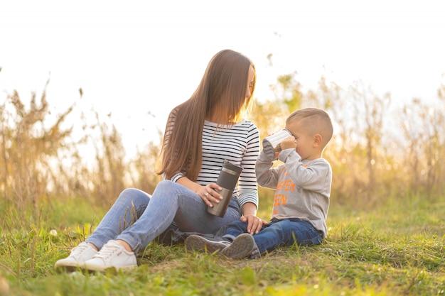秋の散歩に幸せな家族。幼い息子を持つ若い美しい母親は、自然を楽しむ