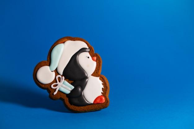 Пряничное печенье милого пингвина с подарком на синем фоне