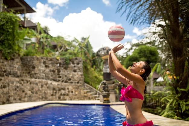Стройная девушка-модель в сексуальном розовом купальнике играет в мяч в тропическом бассейне
