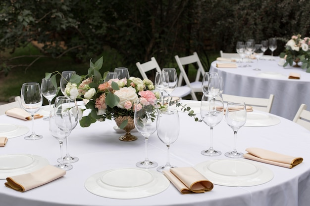真ちゅう製の花瓶に生花で飾られた結婚式のテーブルセッティング。緑の自然の景色を望む屋外のゲスト用の宴会テーブル