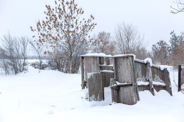 冬のフィールドでボードから古い放棄された建物