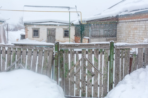 村の冬。木の板の古い老朽化したガタガタのフェンス。たくさんの雪