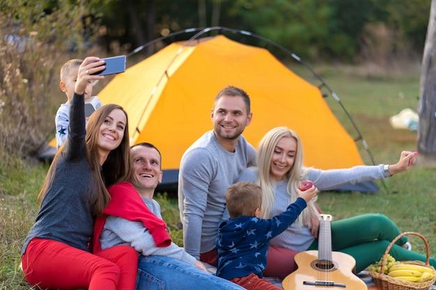 Селфи друзей на природе. друзья отдыхают у озера. отличная веселая компания. большая семья собралась на каникулы. дети и родители на пикнике в летнем лесу.