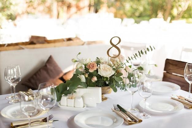 真ちゅう製の花瓶に生花で飾られた結婚式のテーブルセッティング。屋外のゲストのための宴会テーブル