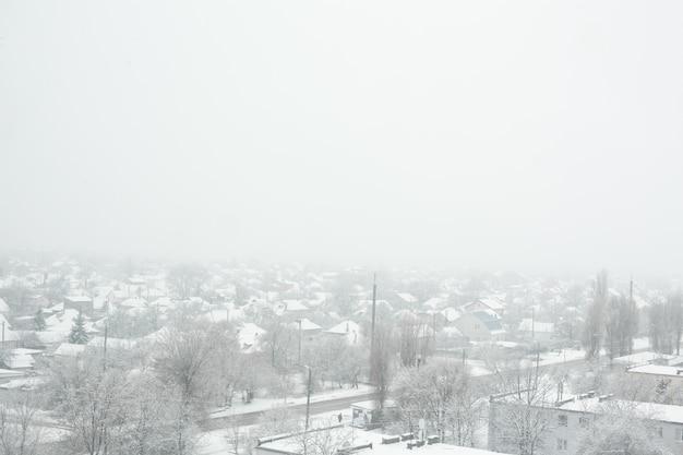 Снежная метель в маленьком городке. все покрыто белым снегом.