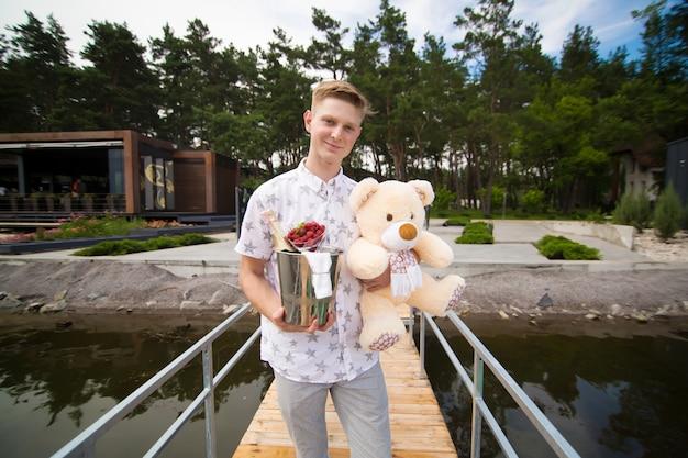 Молодой симпатичный парень ждет встречи со своей девушкой. ожидание на пирсе с шампанским и плюшевым мишкой. романтическое свидание.