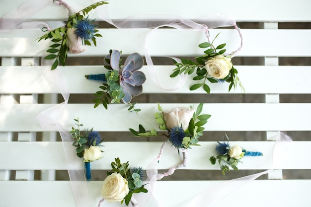 Свежие цветочные мини букеты на белом деревянном декоративном заборе