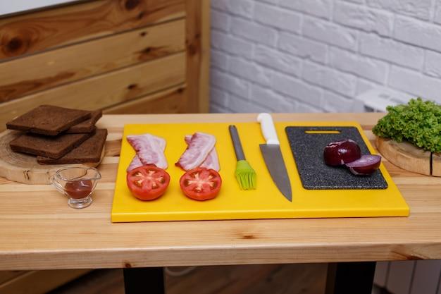 サンドイッチを調理します。木製のテーブルに用意されたすべての成分