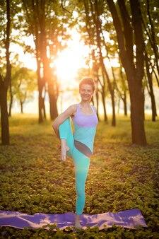 若いスポーツ少女は、やめられた緑の夏の森、ヨガのアサンの姿勢でヨガを練習します。瞑想と自然との一体感