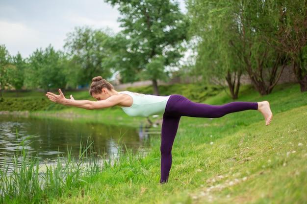 Худенькая брюнетка выполняет летом позы йоги на зеленой лужайке у озера