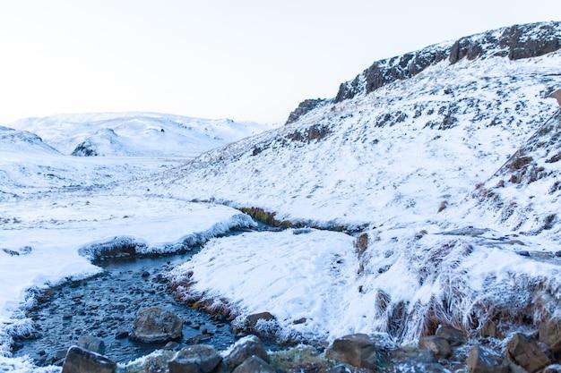 Невероятный зимний пейзаж исландии. зимой источник горячей воды течет в горах.