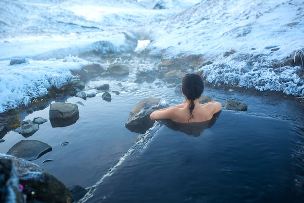 Девушка купается в горячем источнике на открытом воздухе с великолепным видом на снежные горы. невероятная исландия зимой
