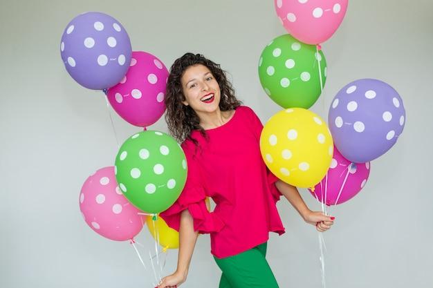 色の風船を持つ美しいかわいい陽気な女の子。休日の誕生日。