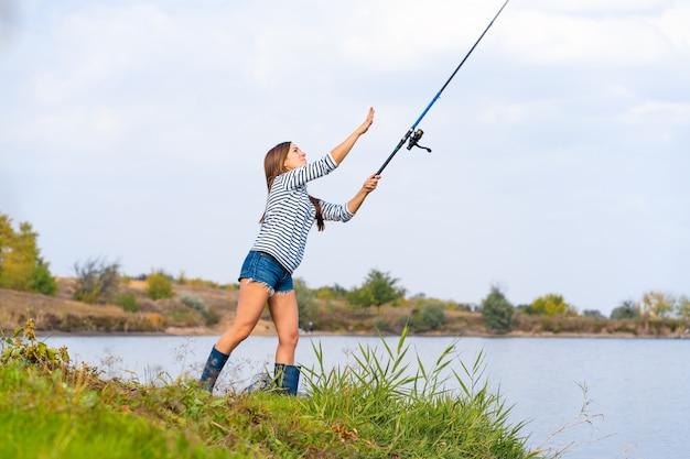 Красивая молодая девушка рыб на озере.