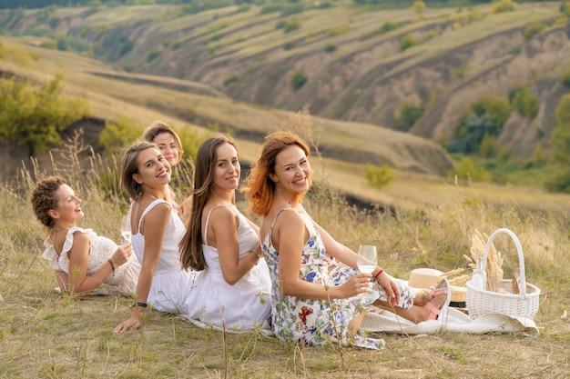白いドレスを着た陽気な女性の友人の会社は、緑の丘の景色を楽しみ、ピクニックでリラックスします。