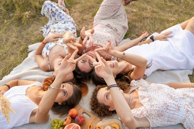 Вид сверху. компания красивых подружек развлекается и устраивает пикник на природе