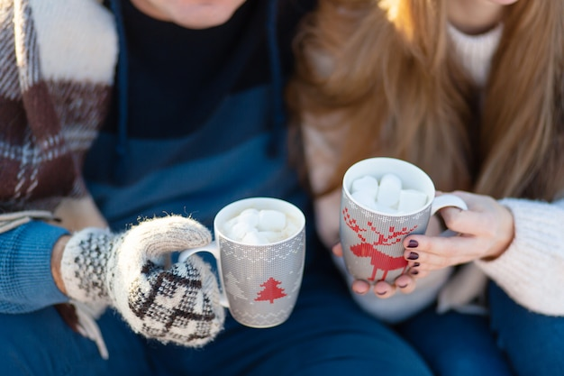 Молодая влюбленная пара пьет горячий напиток с зефиром, сидя зимой в лесу, заправляясь теплыми, удобными ковриками и наслаждаясь природой