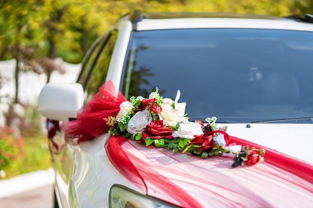 新鮮な花で飾られた白い結婚式の車。結婚式の装飾。