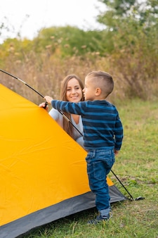 Счастливая семья с маленьким сыном создали палатку. счастливое детство, поход с родителями. ребенок помогает установить палатку