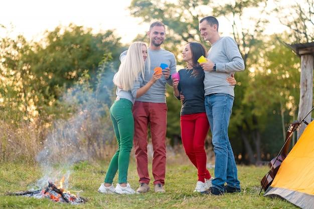 火事で友達とピクニック。ハイキングピクニック自然背景を持つ会社の友人。友達が物語を語る。夏のピクニック。友達と楽しんでください